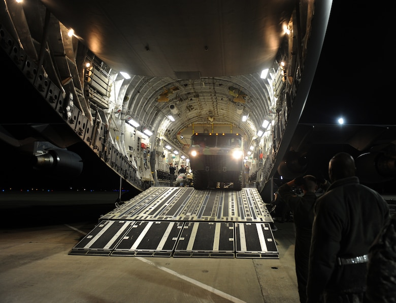 LANGLEY AIR FORCE BASE, Va. -- An M1120 Heavy Expanded Mobility Tactical Truck Load Handling System backs into a C-17 Globemaster III from the 436th Airlift Wing, Dover Air Force Base, Del. Jan. 19.  Personnel from Langley and U.S. Army Fort Eustis worked together to load the C-17 as part Operation Unified Response to aid Haiti after the earthquakes. (U.S. Air Force photo/Senior Airman Zachary Wolf)