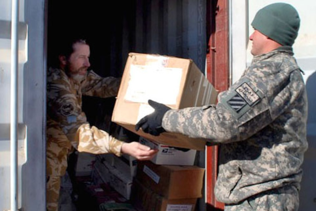Army Chief Warrant Officer 2 Jeffrey Stackhouse carries a box of supplies to Leon O'Flynn, chaplain for the New Zealand Provincial Reconstruction Team, Jan. 13, 2010, in Afghanistan. U.S. Army photo by Spc. Monica K. Smith