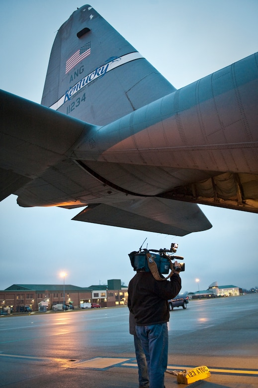 A member of the news media shoots video as the 123rd Airlift Wing prepares to load equipment and relief supplies onto a C-130 aircraft at the Kentucky Air National Guard Base in Louisville, Ky., on Jan. 22, 2010, for a flight to the Dominican Republic as part of earthquake relief efforts in Haiti. The flight was one of three C-130s that left from the unit today, along with approximately 45 Kentucky Air National Guardsmen. The troops are establishing an air cargo hub at Maria Montez International Airport that will be responsible for controlling incoming aircraft, offloading relief supplies and staging them for further movement into Haiti. (U.S. Air Force photo by Maj. Dale Greer)