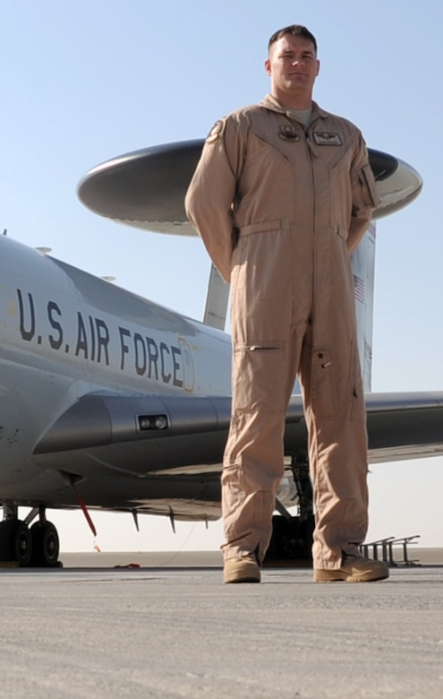 First Lt. Sean Fazande is an air weapons officer with the 965th Expeditionary Airborne Air Control Squadron at a non-disclosed base in Southwest Asia. Here he is pictured with the main airframe, the E-3 Sentry Airborne Warning and Control System aircraft, that he flies on to do is job. Deployed from the 965th AACS at Tinker Air Force Base, Okla., the lieutenant is a prior U.S. Navy aircraft mechanic who became an Air Force officer. The lieutenant's hometown is Destrehan, La.  (U.S. Air Force Photo/Tech. Sgt. Scott T. Sturkol/Released)
