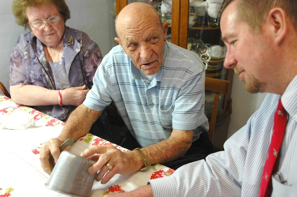 Robert Freese, center, tells James Bement the story behind the etchings in his canteen cup. During World War II, Mr. Freese etched the names of all the places he saw during his combat tour. Mr. Bement recently wrote a book from the perspective of the 93-year-old veteran and his wife, Leona, drawing on their wartime correspondence.(Air Force photo by Howdy Stout)