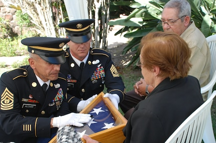 Command Sgt. Maj. Eloy Alcivar, Joint Task Force-Bravo Command Sergeant Major, and First Sgt. Mark Baker, 1/228th Aviation Regiment First Sergeant, present an American flag to Delia Soto, the Honduran mother of a fallen U.S. Soldier, during a memorial ceremony in Siguatepeque, Honduras, Jan 23. Danilo Soto, Jr. (Feb. 18, 1946 - Nov. 15, 2009) was an American citizen and Vietnam War veteran who served in the U.S. Army from 1966 to 1968. (U.S. Air Force photo by 1st Lt. Jen Richard)