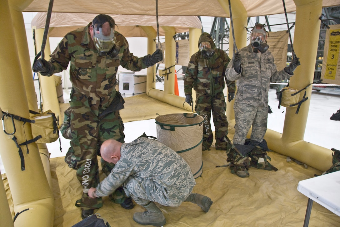 An instructor demonstrates the proper way to remove contaminated outergarments after exposure to simulated chemical agents during at ASTO exercise in the Main Hangar of the Kentucky Air National Guard Base in Louisville, Ky., on Dec. 12, 2009. (United States Air Force by Senior Airman Maxwell Rechel)
