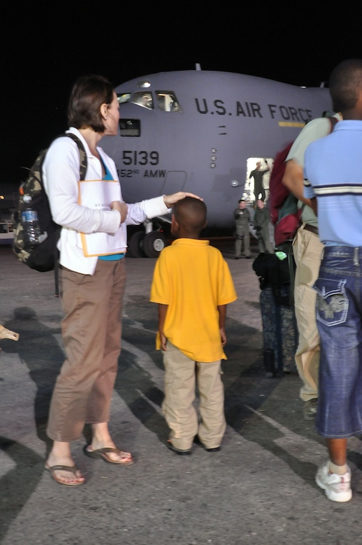Ms. Erin Pemungia and her newly adopted son, Noah, age 7, wait to board an Air Force Reserve C-17 aircraft from the 452nd Air Mobility Wing, March Air Force Base, Calif. The aircraft traveled to Port-au-Prince Jan. 22 to deliver 15 personnel and equipment from the 419th Fighter Wing's 67th Aerial Port Squadron. The 67th APS members will be deployed to Port-au-Prince for at least 45 days and will assist with airfield operations. The aerial porters, all volunteers, will help pave the way for increased U.S. humanitarian aid in the aftermath of last week's devastating earthquake. Prior to returning to the United States, the C-17 took on 54 passengers, including Ms. Pemungia and Noah. Most were Haitian orphans traveling to the U.S. to be united with their adoptive parents. (U.S. Air Force Photo/Kari Tilton)