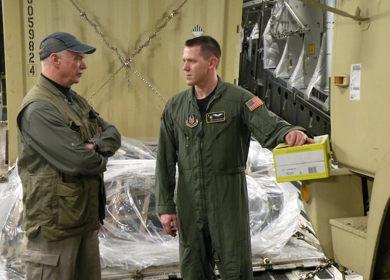 David Wood, a reporter with politicsdaily.com, chats with Staff Sgt. Steve Pinkerton, a Reserve loadmaster with the 317th Airlift Squadron, Charleston, Air Force Base, S.C. while flying on a C-17 to Haiti in support of Operation Unified Response Jan. 22, 2010. (U.S. Air Force Photo/Master Sgt. Steve Staedler)