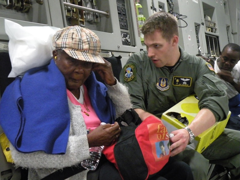 Staff Sgt. Gus Morse, a Reserve C-17 loadmaster from the 317th Airlift Squadron, Charleston Air Force Base, S.C., helps a Haitian woman insert her ear plugs prior to departure to Orlando during the early morning hours of Jan. 22, 2010. (U.S. Air Force Photo/Master Sgt. Steve Staedler)