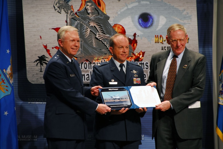 DAYTON, Ohio -- (left to right) Brig. Gen. John F. Thompson, the Air Force's Program Executive Officer for Intelligence, Surveillance and Reconnaissance and Commander of the 303rd Aeronautical Systems Wing; Col. Christopher Coombs, Commander of the 703rd Aeronautical Systems Group; and Museum Director Maj. Gen. (Ret.) Charles D. Metcalf participate in the MQ-9 Reaper exhibit opening at the National Museum of the U.S. Air Force on Jan. 25, 2010. (U.S. Air Force photo)