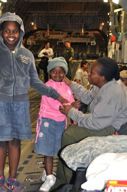 Alene, right, and her granddaughters, ages 9 and 6, travel from Port-au-Prince, Haiti, to Orlando, Fla., aboard a C-17 aircraft Jan. 22. The threesome joined 51 other passengers en route to the United States to reunite with extended family members. (U.S. Air Force photo/Bryan Magaña)