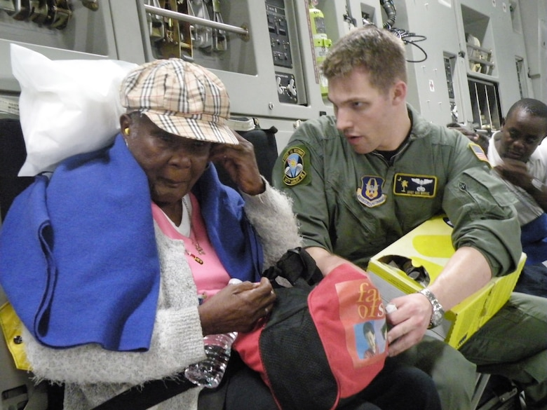 Staff Sgt. Gus Morse helps a Haitian woman insert her ear plugs before departure to Orlando, Fla., during the early morning hours of Jan. 22, 2010, in Haiti. Sergeant Morse is a 317th Airlift Squadron loadmaster from Charleston Air Force Base, S.C. (U.S. Air Force photo/Master Sgt. Steve Staedler)