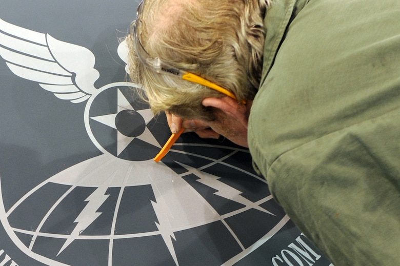 "WHITEMAN AIR FORCE BASE, Mo. - Brian Geary, 509th Maintenance Squadron structural maintenance low-observable technician, uses a rubber tool to peel off the stencil from around the newly-sprayed Air Force Global Strike Command patch on a B-2 Spirit, Jan. 25, 2010. On Feb. 1, 2010, Whiteman AFB and its arsenal of 20 B-2 bombers will change commands from Air Combat Command to AFGSC. The mission of AFGSC is to ""develop and provide combat-ready forces for nuclear deterrence and global strike operations -- safe -- secure -- credible to support the President of the United States and combatant commanders."" (U.S. Air Force photo by Airman 1st Class Carlin Leslie) (Released)"