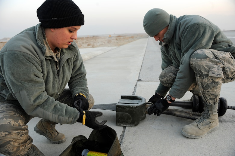 BAGRAM AIRFIELD, Afghanistan--U.S. Air Force Senior Airman Melissa Gillett (near), and Staff Sgt. Eric Austin, 455th Expeditionary Civil Engineer Squadron, maintain an arresting cable at Bagram Airfield, Jan. 15, 2010. Gillett is from Duluth, Minn., and Austin is from Superior, Wis., both are members of the Minnesota National Guard. (U.S. Air Force photo by: Tech. Sgt. Jeromy K. Cross)