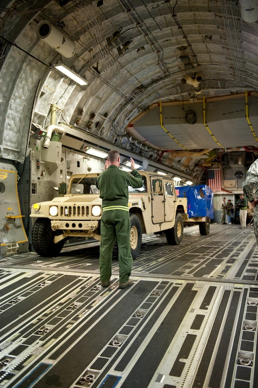 Air Force Tech. Sgt. Cecil Dickerson, a loadmaster from the Alaska Air National Guard?s 249th Airlift Squadron, directs an Army Humvee onto a Mississippi Air National Guard C-17 aircraft at the Kentucky Air National Guard Base in Louisville, Ky., on Jan. 27, 2010. The Humvee, along with 90 tons of other equipment and about 40 soldiers from the 3rd Sustainment Command (Expeditionary), were deploying to Port-au-Prince, Haiti, for earthquake relief efforts as part of Operation Unified Response. The Fort Knox, Ky.-based unit is expected to stay in Haiti for up to six months. (U.S. Air Force photo by Maj. Dale Greer/Released)