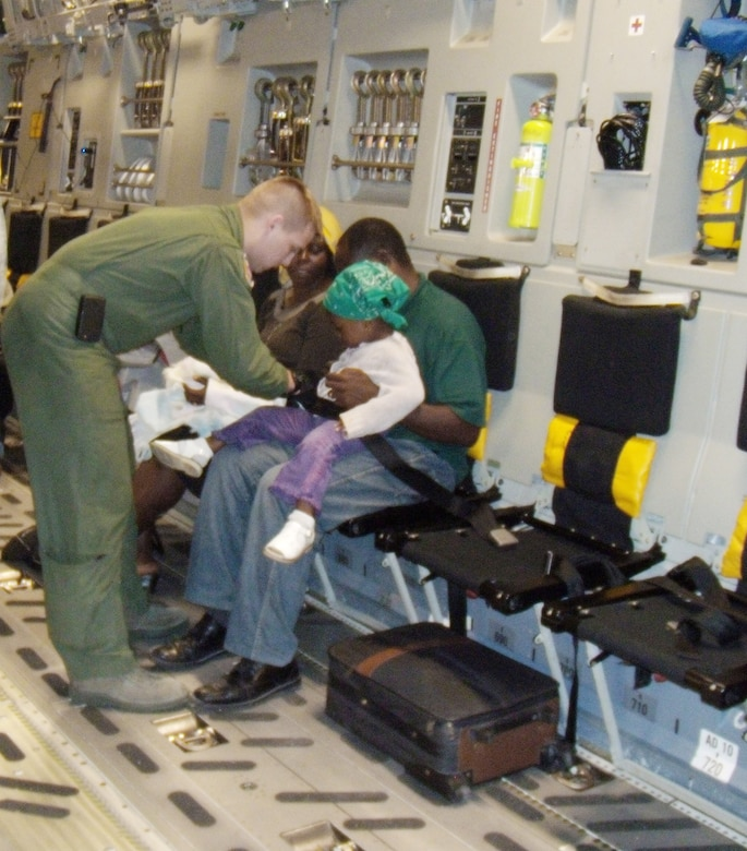 Airman 1st Class Landon Greenwood helps buckle in a young girl being evacuated on a C-17 Globemaster III to the U.S. Jan. 19, 2010, from Port-au-Prince, Haiti,. The C-17 aircrew had delivered 90,000 pounds of cargo and was boarding 36 evacuees in support of Operation Unified Response.  Airman Greenwood is a loadmaster with the 3rd Airlift Squadron at Dover Air Force Base, Del.  (U.S. Air Force photo/2d Lt Abigail Wise)