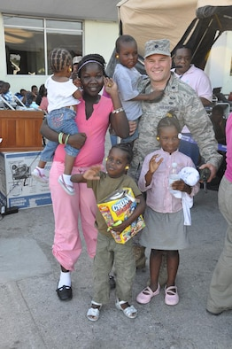 Lt. Col. Randon Draper, 18th Air Force Legal Office, spends a few moments wtih the first five Haitian children that he helped send to their adoptive parents after the devastaging 7.0 earthquake there Jan. 12.  He's been on the ground at Port-au-Prince since Jan. 14 and has helped immigration and state department officials expedite valid adoptions for several hundred children. (courtesy photo)