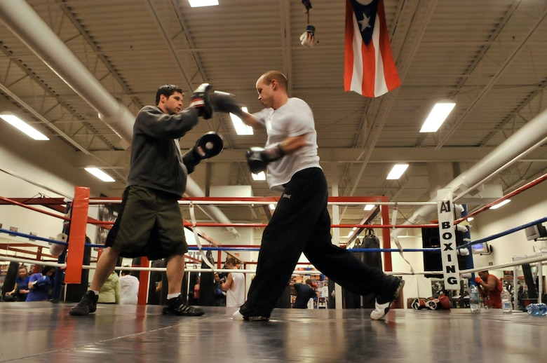 AURORA, Colo. -- Staff Sgt. Joshua Hinton, Air Reserve Personnel Center Directorate of Communications and Information knowledge operations manager, right, trains in the ring with professional boxer and A1 Boxing trainer Terry Bergl Oct. 21. Boxing fitness programs are full body workouts that can burn 800 to 1,000 calories for every one hour session. (U.S. Air Force photo by Senior Airman Kathrine McDowell)