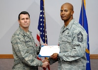 NELLIS AIR FORCE BASE, Nev.-- Col. John P. Montgomery, 98th Range Wing commander, presents Chief Master Sgt. Mark T. Darden, 98th Range Wing superintendent, with a Bronze Star Jan. 14 for his meritorious achievement while deployed to Joint Base Balad, Iraq and Al Udeid Air Base, Qatar.  Chief Darden served as the Chief Enlisted Manager for the 557th Expeditionary RED HORSE Squadron, 9th Air Expeditionary Task Force from Sept. 13, 2008 to April 1, 2009.  (U.S Air Force photo by Staff Sgt Taylor Worley)