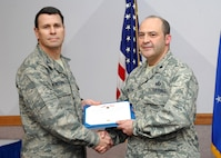NELLIS AIR FORCE BASE, Nev.-- Col. John P. Montgomery, 98th Range Wing commander, presents Lt. Col. Tony L. Millican, 98th Mission Support Group deputy commander, with a Bronze Star Jan. 13 for his meritorious service while deployed to Kabul, Afghanistan.  Colonel Millican  served as the commander of the United States National Support Element, Headquarters International Security Assistance Force from March 1 to Sept. 1. (U.S Air Force photo by Staff Sgt Taylor Worley)