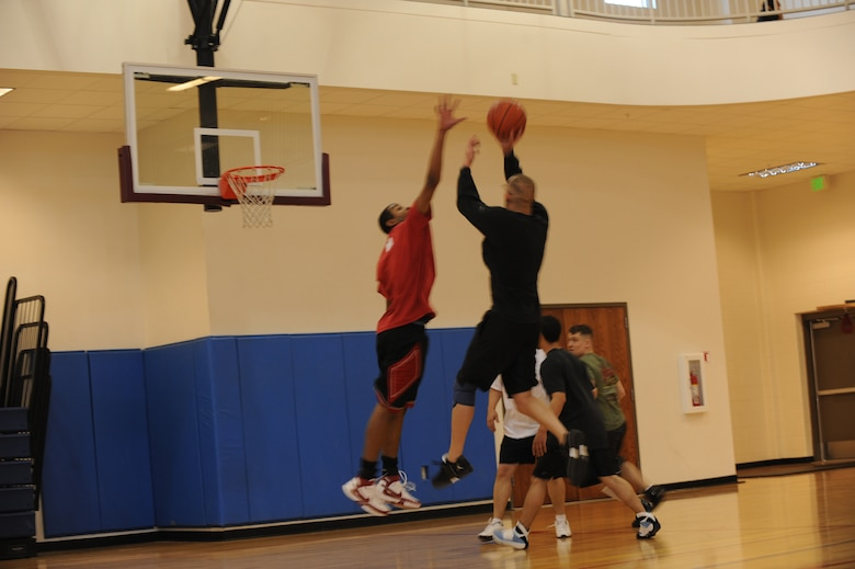 BUCKLEY AIR FORCE BASE, Colo. -- Marine Corps Staff Sgt. Joseph Barotti, Marine Air Control Squadron 23, shoots a fadeaway while Staff Sgt. Alfred Davis with the 4th Manpower Requirements Squadron, tries to block the shot during the 3 on 3 Hoops Classic at the base Fitness Center Jan. 27. (U.S. Air Force by Airman 1st Class Marcy Glass)