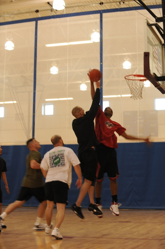 BUCKLEY AIR FORCE BASE, Colo. -- Staff Sgt. Alfred Davis, 4th Manpower Requirements Squadron, blocks Marine Corps Staff Sgt. Joseph Barotti, Marine Air Control Squadron 23, as he goes up for a shot during the 3 on 3 Hoops Classic at the base Fitness Center Jan. 27. (U.S. Air Force by Airman 1st Class Marcy Glass)
