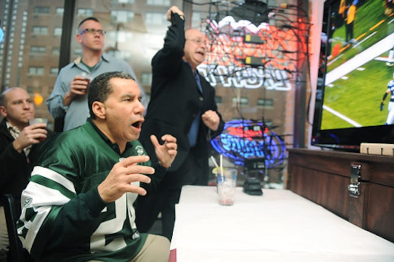 Master Sgt. Scott Dixon, loadmaster, 107th Airlift Wing (blue shirt) looks on as New York State Governor David Paterson (Jets jersey) cheers for the New York Jets. The sergeant along with other 107th AW members that had return from Haiti, in support of Operation Unified Response were invited to New York City to cheer the Jets onto victory with the governor. Well there's always next year. (Courtesy photo)