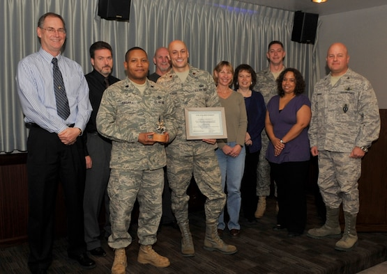 Col. Jim Jennings (right) 21st Space Wing vice commander, presented the October Golden Knight award for teamwork between the 21st Comptroller Squadron and the 21st Contracting Squadron for end of year closeout purchasing. (Air Force photo by Rob Bussard)
