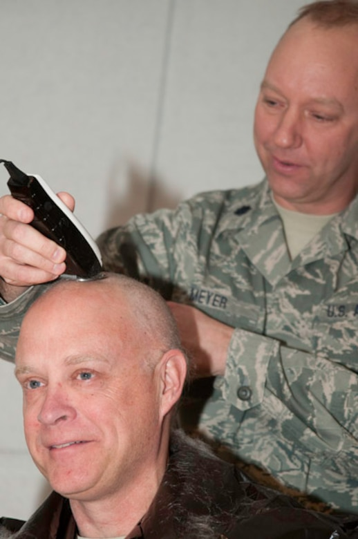 After receiving the grade of outstanding after a recent inspection, as promised, Colonel Andy Halter, 139th maintenance group commander, surrendered his hair on stage, January 11, 2010. Capt. Orth and Lt.Col. Gordon Meyer, 139th Maintenance, were happy to oblige the group commander. (U.S. Air Force photo by Master Sgt. Shannon Bond)