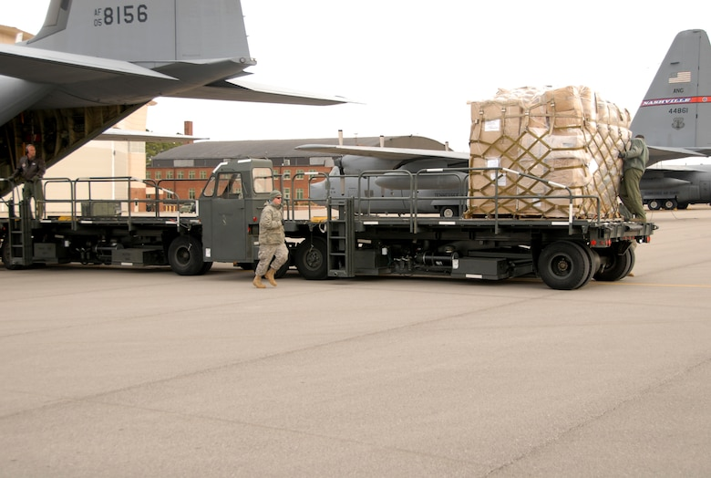Staff Sgt. Anthony Boss, runs to help two reservists from the 403rd Wing, Keesler AFB, Miss., load pallets onto a C-130 at the 118th AW Jan. 28. The crew loaded eight of 21 pallets to be sent to Aghanistan as Humanitarian Aid. The next group of pallets is scheduled to be loaded sometime in February.