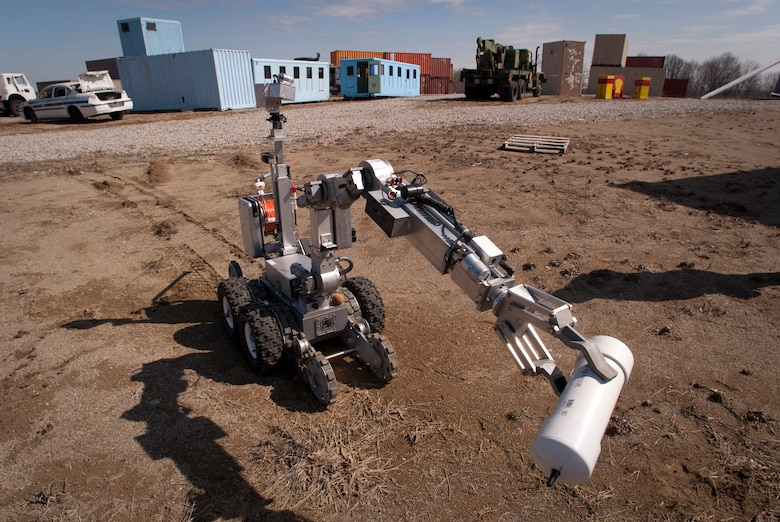 A Remotec MK VI Andros robot, steered remotely by a Kentucky Air National Guard explosive ordnance disposal technician, carries a simulated pipe bomb to a secure location to be x-rayed during a training evolution at Camp Atterbury, Ind. By x-raying the suspect devic,e Airmen are able to determine the explosive capabilities of the device and properly disrupt it. (U.S. Air Force photo/Tech. Sgt. D. Clare)