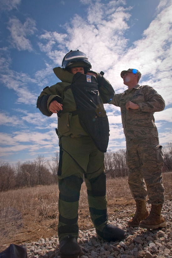 Staff Sgt. Matthew ?Mouse? Meuser helps fellow explosive ordnance disposal technician Tech. Sgt. Lowery Woods adjust his EOD 8 bomb suit before proceeding to x-ray a simulated pipe bomb during a training evolution at Camp Atterbury, Ind.  Kentucky Air National Guard Sergeants Meuser and Woods were on a training evolution after clearing the Indiana National Guard?s range of expended ordnance. (U.S. Air Force photo/Tech. Sgt. D. Clare)