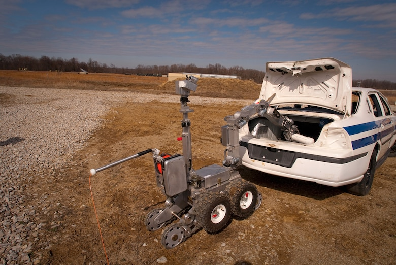 A Remotec MK VI Andros robot, steered remotely by a Kentucky Air National Guard explosive ordnance disposal technician, removes a simulated pipe bomb from a suspicious vehicle during a training evolution at Camp Atterbury, Ind. In addition to clearing the Camp Atterbury Air-to-Ground Gunnery Range for the Indiana National Guard, the Kentucky Airmen were able to get hands-on experience that will sharpen their skills for a variety of real world missions. (U.S. Air Force photo/Tech. Sgt. D. Clare)