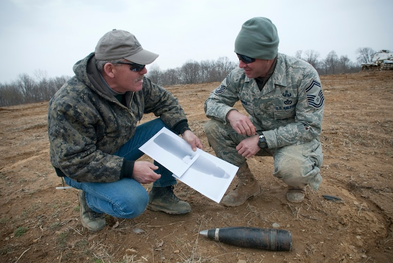Sergeant Andy Squier, an Indiana State Police hazardous devices technician, and Senior Master Sgt. Lou Corner, Kentucky Air National Guard EOD superintendent, discuss an x-ray of a 90mm high explosive shell at the Camp Atterbury Air-to-Ground Gunnery Range, Camp Atterbury, Ind. The shell, which was turned in to the Indiana State Police and detonated by Kentucky and Indiana EOD techs, could have caused serious harm if it had exploded in a residential environment. (U.S. Air Force photo/Tech. Sgt. D. Clare)