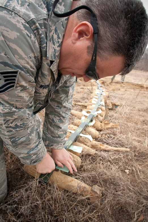 Tech. Sgt. Lowery Woods of the Kentucky Air National Guard attaches C-4 plastic explosives to a row of 25-pound practice bombs at the Camp Atterbury Air-to-Ground Gunnery Range in Indiana. (U.S. Air Force photo/Tech. Sgt. D. Clare)