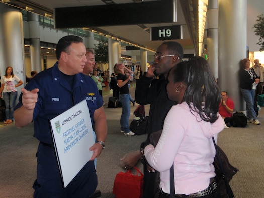 Cmdr. Jeff Pashai; U.S. Southern Command Coast Guard TCA liaison; greets two Haitian coast guard members at the Miami International Airport; Jan. 23. The Haitian military members are part of the International Military Exchange Training program and have spent the past six to eight months studying in the U.S. With the help of multiple U.S. military service; seven students found the means to travel back to Haiti and reunite with family members. (U.S. Air Force photo by Senior Airman Danielle Grannan)