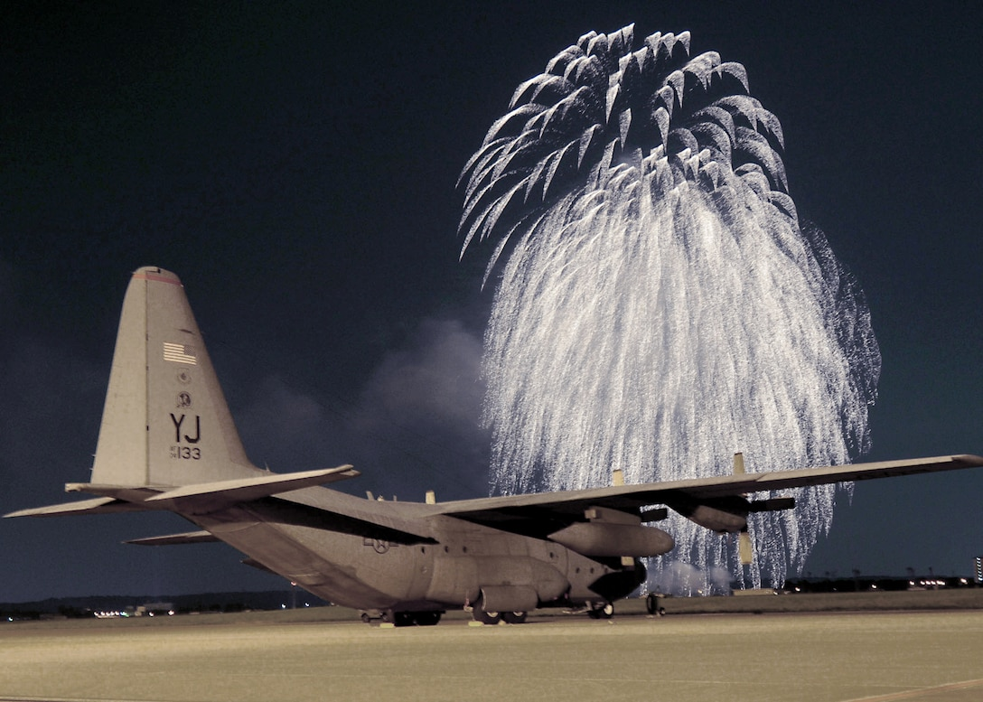 Fireworks erupt in front of a C-130 Hercules on the flightline at Yokota Air Base, Japan, at the Independence Day festivities in 2009. The 374th Force Support Squadron provided events for Yokota residents and their guest of all ages.  (U.S. Air Force photo/Staff Sgt. Veronica Pierce)