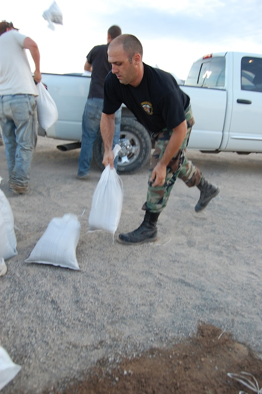 Staff Sgt. Rodney Massengill, of Cheyenne, Wyo., a member of the Wyoming Air National Guard's 153rd Medical Group, tosses sandbags in an effort to mitigate rising flood waters of the Popo Agie River, in Fremont County, Wyoming.  Massengill is assigned to the Wyoming National Guard Task Force 2-300th, for this state active duty mission. (Released)