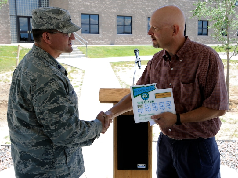 BUCKLEY AIR FORCE BASE, Colo. -- Keith Wood, a Colorado State Forester, presents Lt. Col. William Morrison, 460th Mission Support Group deputy commander, the Tree City USA award during the Arbor Day Celebration June 30. (U.S. Air Force photo by Staff Sgt. Dallas Edwards)