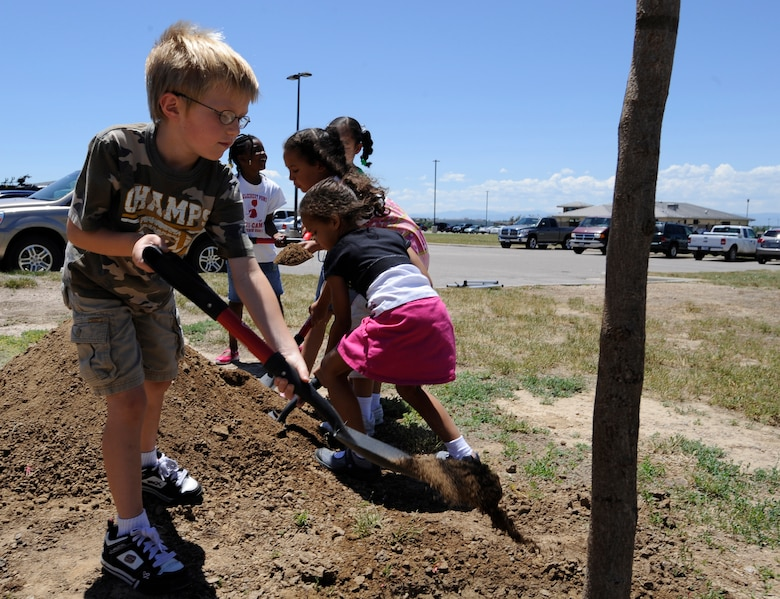 BUCKLEY AIR FORCE BASE, Colo. -- Six-year-old Conner Miller, a base dependent, places soil at the base of a newly planted tree during the Arbor Day celebration June 30. (U.S. Air Force photo by Staff Sgt. Dallas Edwards)