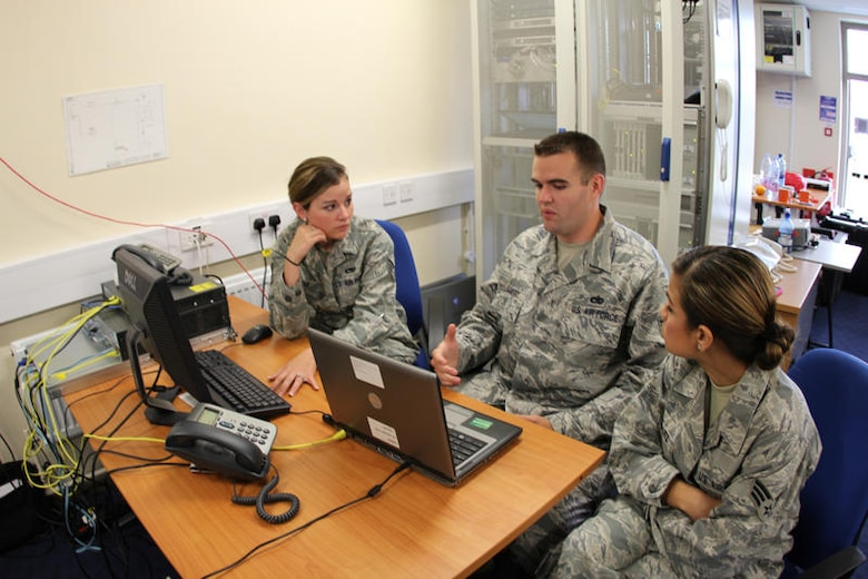 Staff Sgt. Mary Medina, 52nd Combat Communications Squadron and Staff Sgt. Gabriel Scarberry 373rd Training Squadron and Senior Airman Denise Gonzalez, 52nd CBCS discuss the technical data of the solution to configuration of their US Voice over Internet Protocol (VoIP) equipment to provide a solution to speak with their British counterparts system.  Training on this new process was a big benefit to the team's time at United Architecture 2010.  UA2010 is a US-UK interoperability communications exercise held at RAF Lemming, United Kingdom June 21 to July 2. (US Air Force photo by Master Sgt. Robert Talenti)