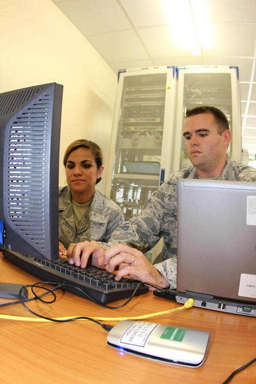 Staff Sgt. Gabriel Scarberry 373rd Training Squadron and Senior Airman Denise Gonzalez, 52nd Combat Communications Squadron discuss the solution that has bridged US and UK Secure Voice over Internet Protocol (VoIP) communications during United Architecture 2010.  UA2010 is a US-UK interoperability communications exercise held at RAF Lemming, United Kingdom June 21 to July 2. (US Air Force photo by Master Sgt. Robert Talenti)