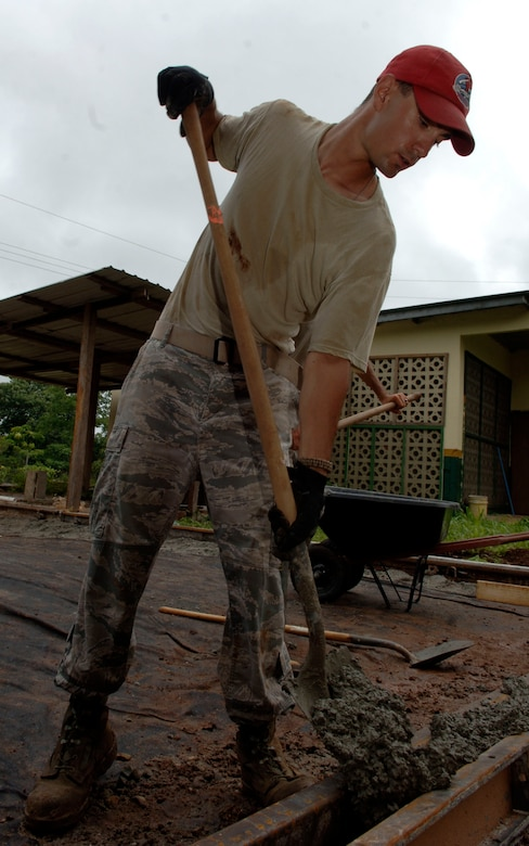 Senior Airman Randall Minor, 820th Expeditionary RED HORSE Squadron, shovels concrete into a form at Rio Iglesia Medical Clinic July 2. (U.S. Air Force photo/Tech. Sgt. Eric Petosky)