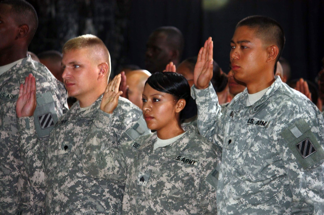 U.S. troops take the citizenship oath during a naturalization ceremony in Al Faw Palace on Camp Victory, Iraq, July 4, 2010. More than 150 servicemembers became citizens in a ceremony attended by Vice President Joe Biden and his wife, Jill Biden.