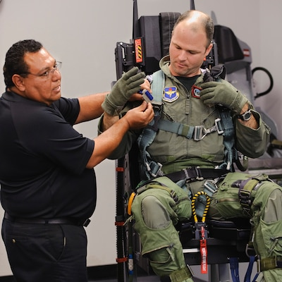 Rey Gutierrez, 12th Operational Support Squadron, goes over  procedures for connecting parachute harnesses to the new T-38C ejection seat while Maj. Bryan France, 435th Flying Training Squadron, connects his harness shoulder straps to the seat June 30. The new seat replaces the carried parachute with a harness and in-seat chute, has zero/zero capability and includes a redesigned parachute.(U.S. Air Force photo/Steve Thurow)