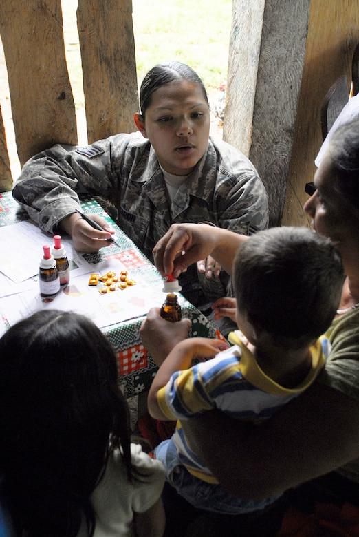 LOS PLANES, Honduras --  Staff Sgt. Dulce Caron, a 612th Operations Support Squadron interpreter, goes over the usuage of vitamins and supplements with a Honduran family here June 28. Sergeant Caron was part of a medical readiness training exercise in which the Joint Task Force Bravo Medical Element assisted the Honduran Ministry of Health and South Dakota State University students in assessing the nutritional needs of Honduran children in rural areas. (U.S. Air Force photo/Tech. Sgt. Benjamin Rojek)