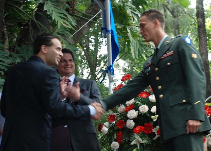 Spc. Eniol Abreusarmiento, a helicopter mechanic and crew chief in the 1-228th Aviation Regiment, Soto Cano Air Base, Honduras, shakes hands with Emigdio Martinez, the field office director for the Office of Citizenship and Immigration Services, after taking the naturalization oath during a ceremony in Tegucigalpa July 2. Specialist Abreusarmiento, who was born in Cuba, became a U.S. citizen at an Independence Day celebration hosted by U.S. Ambassador to Honduras Hugo Llorens and attended by Honduran President Porfirio Lobo. (U.S. Air Force photo by 1st Lt. Jen Richard)
