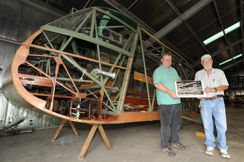 WHITEMAN AIR FORCE BASE, Mo. - Frank McKinley, of the Whiteman Heritage Foundation, and Robert Rainey, Waco glider restoration project volunteer, hold an artist's rendition of a Waco glider in flight while standing in front of the original glider they are restoring, July 6.   In 1942, U.S. Army Air Corps officials selected the site of present-day Whiteman AFB to be the home of Sedalia Army Air Field, a training base for Waco glider pilots. (U.S. Air Force photo/ Senior Airman Carlin Leslie)(Released)