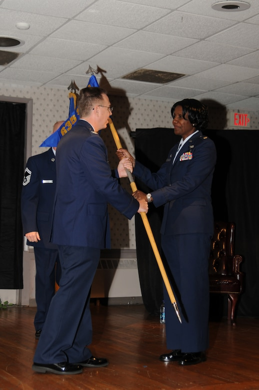 Colonel Scott J. Tew, Commander, 635th Supply Chain Operations Group, hands over the 437th Supply Chain Operations Squadron guidon to Major Majornetta Alexander, Commander of the Headquarters Illinois Air National Guard Detachment 2 and Chief of the 635th Supply Chain Management Group (SCMG) Management and Division Systems, Scott Air Force Base, Ill., during her assumption of leadership of the newly formed 437th Supply Chain Operations Squadron (SCOS), July 8 at Scott AFB. Her appointment as director of the 437th SCOS makes her the first Illinois Air National Guard officer to be appointed to such a position under the Air Force's Total Force Initiative.