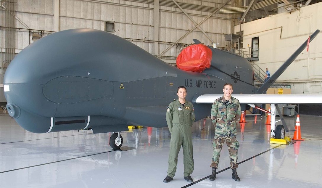 (Left) Cadets First Class Jeremy Granow and Austin Kootz pose in front of a Global Hawk during their three-week U.S. Air Force Academy Cadet Summer Research Program tour with the Air Force Operational Test and Evaluation Center's Detachment 5 at Edwards AFB, Calif. Both cadets designed a user-friendly database for the programs Global Hawk, Predator, Battlefield Airborne Common Node, Multi-Platform-Radar Technology Insertion Program, and Advance Signals Intelligence Platform. (U.S. Air Force photo).