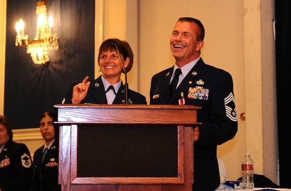 OFFUTT AIR FORCE BASE, Neb. - Command Chief Master Sgt. Lisa Sirois and her husband, Chief Master Sgt. Roger Sirois, are all smiles while they thank those in attendance at their dual retirement ceremony at the Patriot Club, July 6.  With over 60 years of combined service, Chiefs Lisa and Roger Sirois' retirement ceremony symbolized both a commitment to the service of this country as well as one another.U.S. Air Force Photo by Josh Plueger