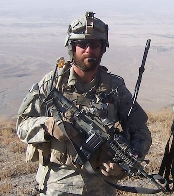"""TACP with Gear: A bearded TACP member with a few indispensables.  TACPs imbedded with Special Forces units are sometimes allowed to grow beards and long hair, euphemistically referred to as """"relaxed-grooming standards."""""""