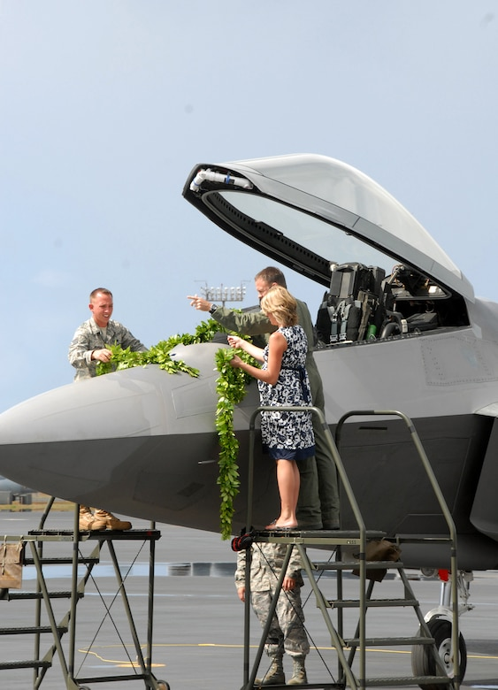 """Lt. Col. Harvey """"Banger"""" Newton, pilot 19th Fighter Squadron, along with his wife and Staff Sgt. Joel Herman, an active duty F-22 Raptor crew chief assigned to the 154th Wing Aircraft Maintenance Squadron, Hawaii Air National Guard, drape maile lei across the nose of the F-22 Raptor during the F-22 Arrival Ceremony July 9, on Joint Base Pearl Harbor-Hickam, Hawaii. Maile lei is part of a Hawaiian tradition used to mark important occasions. The arrival of the F-22 Raptor marks the beginning of a new associate unit between the Hawaii Air National Guard and the 15th Wing, active duty Air Force. (U.S. Air Force photo/Tech. Sgt. Betty J. Squatrito-Martin)"""